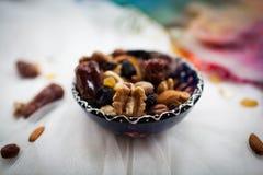 Platte mit den Nüssen und Trockenfrüchten, die auf einer weißen Tabelle liegen Lizenzfreie Stockfotografie