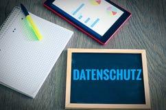 Platte mit der Aufschrift auf Deutsch Datenschutz im englischen Datenschutz mit einer Tablette und einem Block, zum von typischen Lizenzfreie Stockfotografie