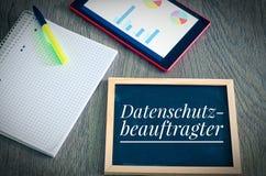 Platte mit der Aufschrift auf Deutsch Datenschutzbeauftragter in englischem Datenschutzbeauftragtem mit einer Tablette und einem  Stockbild