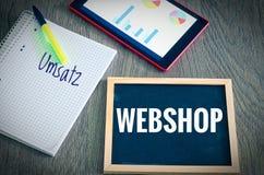 Platte mit der Aufschrift Webshop und das deutsche Wort Umsatz in den englischen Verkäufen mit Diagrammen und Statistiken einer T Lizenzfreie Stockfotos