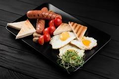 Platte mit englischem Frühstück auf dem schwarzen hölzernen Hintergrund Lizenzfreies Stockfoto
