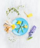 Platte mit Frühlingsblumen, -gabel, -zeichen und -dekoration auf grauem hölzernem Hintergrund, Draufsicht Stockbilder