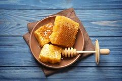 Platte mit frischen Bienenwaben und Schöpflöffel Lizenzfreie Stockfotos