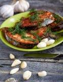Platte mit gebratenen Fischen und Knoblauch auf einer Tabelle Stockfoto