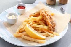 Platte mit geschmackvollen gebratenen Fischen, Chips und Soßen auf Tabelle Lizenzfreie Stockfotos