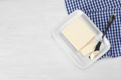Platte mit geschmackvoller frischer Butter und Messer auf Tabelle Lizenzfreie Stockbilder
