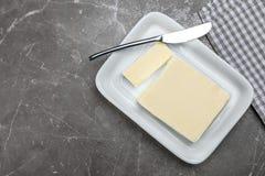 Platte mit geschmackvoller frischer Butter und Messer auf Tabelle Stockfotografie