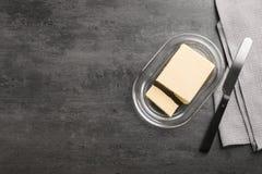 Platte mit geschmackvoller frischer Butter und Messer auf Tabelle Lizenzfreie Stockfotografie
