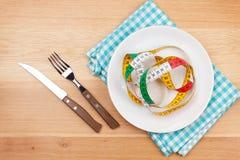 Platte mit Maßband, -messer und -gabel Diätlebensmittel auf hölzernem Vorsprung Stockbilder