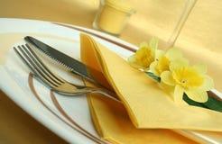 Platte mit Messer und Gabel auf gelber Tischdecke Lizenzfreie Stockfotos