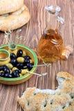 Platte mit Oliven, Brot und Olivenöl Stockbild