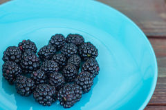 Platte mit reifer frischer organischer Brombeere auf einem hölzernen Hintergrund Stockfoto