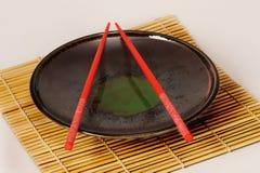 Platte mit roten Ess-Stäbchen Lizenzfreies Stockfoto