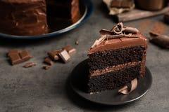 Platte mit Scheibe des geschmackvollen selbst gemachten Schokoladenkuchens auf Tabelle Raum für Text stockbilder