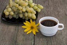 Platte mit Trauben, ein Tasse Kaffee und eine gelbe Blume, noch Stockfotos