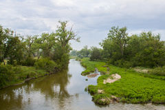 The Platte River in Early Morning. The Platte River peacefully flows by lush grass and trees Royalty Free Stock Photos