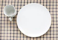 Platte und Cup auf Tischdecke Lizenzfreies Stockfoto