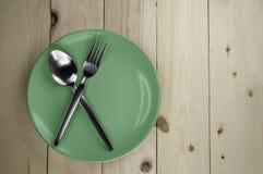 Platte und Tischbesteck auf Holztisch Lizenzfreie Stockfotos