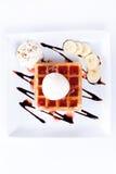 Platte von belgischen Waffeln mit Eiscreme und Schlagsahne, Erdbeersoße und Bananen Stockbild