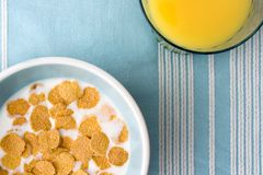 Platte von Frühstückskost aus Getreide und von Glas Orangensaft auf Tabelle-clotch Lizenzfreie Stockfotos