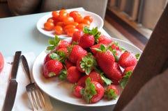 Platte von frischen Erdbeeren und von Kirschtomaten auf dem Tisch nahe dem Fenster Stockfoto