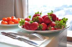 Platte von frischen Erdbeeren und von Kirschtomaten auf dem Tisch nahe dem Fenster Stockfotos
