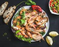 Platte von gebratenen Tigergarnelen und -krake bessert mit frischem Porree, Salat, Pfeffer, Zitrone, Brot, Pestosoße über Schwarz Lizenzfreies Stockfoto