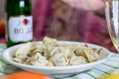 Platte von heißen Mehlklößen mit Dampf und Glas Champagner am Hintergrund auf dem Tisch am Feiertag lizenzfreies stockfoto