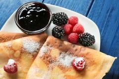 Platte von köstlichen dünnen Pfannkuchen mit Beeren Stockfoto