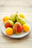 Platte von köstlichen frischen Birnen und von Aprikosen Lizenzfreies Stockbild