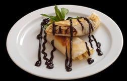 Platte von köstlichen Krepps rollen mit frischen Früchten und Schokolade auf einer weißen Platte stockfoto