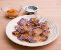 Platte von purpurroten Kartoffelchips, Bad und Salz auf Holztisch Stockfoto