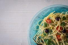 Platte von Spaghettis mit Tomaten, Oliven und frischen Kräutern Lizenzfreie Stockbilder