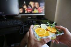 Platte von Zitrusfr?chten in ihren H?nden gegen den Hintergrund von Monitoren und von Computertastatur Gesunde Nahrung stockfotos