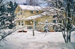 Plattelandshuis door bomen wordt met sneeuw in januari zwaar worden behandeld omringd dat Royalty-vrije Stock Foto