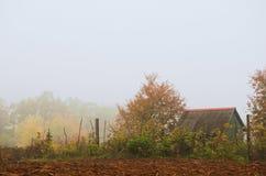 Plattelandshuisje in de herfstbos in mist wordt verpakt die Royalty-vrije Stock Afbeelding