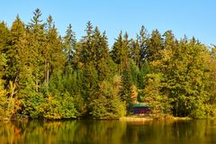 Plattelandshuisje door vijver in de herfst stock afbeelding