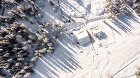 Plattelandshuisje en bomen in sneeuw wordt behandeld die Luchtbeeld in Cortina D ` a stock foto