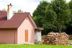 Plattelandshuisje met buiten brandhout stock afbeelding