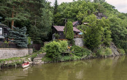 Plattelandshuisje met een boot op de rivierbank Royalty-vrije Stock Afbeeldingen