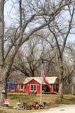 Plattelandshuisje met voor verkoopteken in land onder grote bomen met grasmaaimachines voor verkoop en Amerikaanse en Verbonden v Royalty-vrije Stock Afbeeldingen