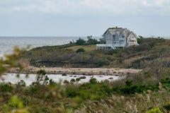 Plattelandshuisje onder struiken en gras, die een rotsachtig strand, Blokeiland, RI overzien royalty-vrije stock afbeelding