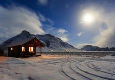 Plattelandshuisje op een achtergrond van bergen in het maanlicht Royalty-vrije Stock Foto's