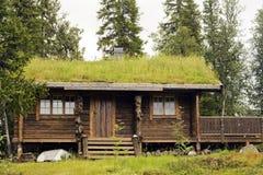 Plattelandshuisje op een bos bij de bergen van Noorwegen. Stock Afbeelding