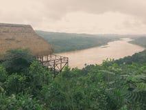 Plattelandshuisje over rivier Stock Foto
