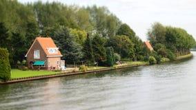 Plattelandshuisjehuis langs de rivieroever met bomen en groen gras Royalty-vrije Stock Fotografie