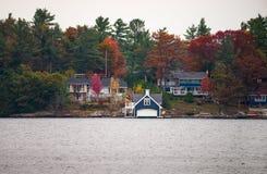 Plattelandshuisjes en een botenhuis op een meer stock foto's