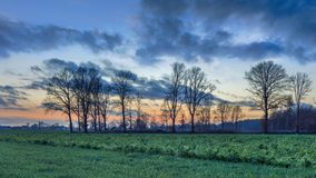 Plattelandslandschap met bomen en een kleurrijke zonsondergang royalty-vrije stock foto