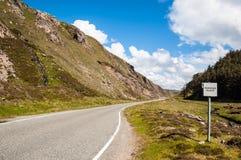 Plattelandsweg in de hooglanden met een voorbijgaand plaatsteken Stock Afbeeldingen