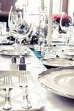 Platten auf dem Tisch mit Lebensmittel und Getränk Stockbild